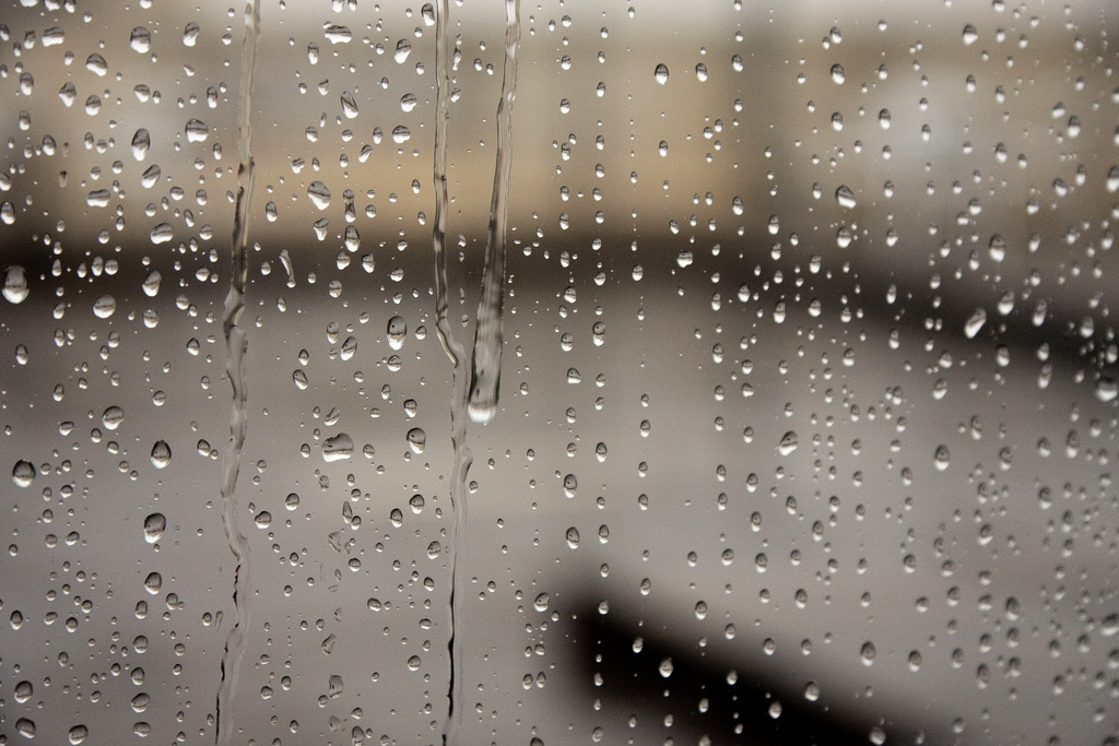 Rain water dripping over a transparent window, between other small droplets of different shapes and sizes.